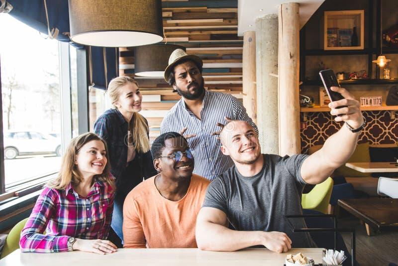 Il gruppo di giovani amici allegri sta sedendo in un caff?, mangiando, beventi le bevande Gli amici prendono i selfies e prendono fotografie stock libere da diritti