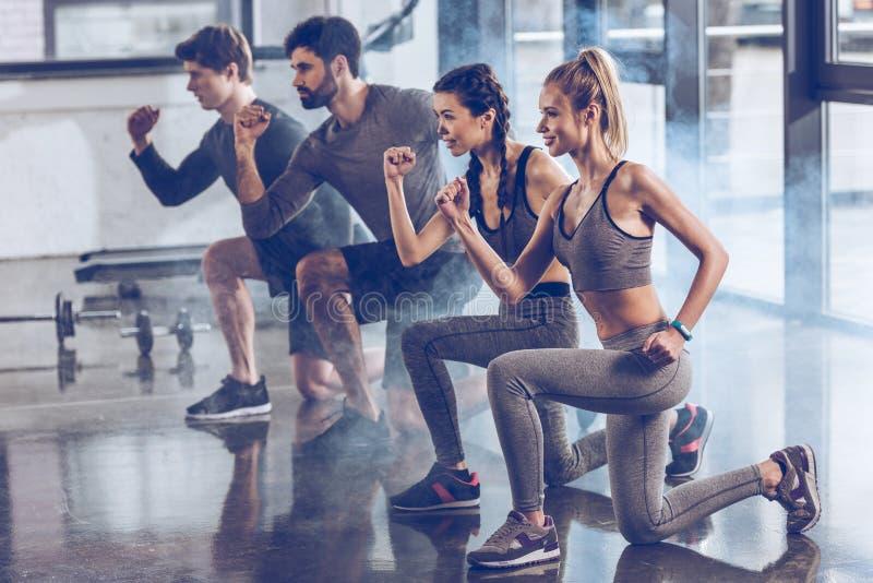 Il gruppo di giovani atletici in abiti sportivi che fanno l'affondo si esercita alla palestra immagini stock
