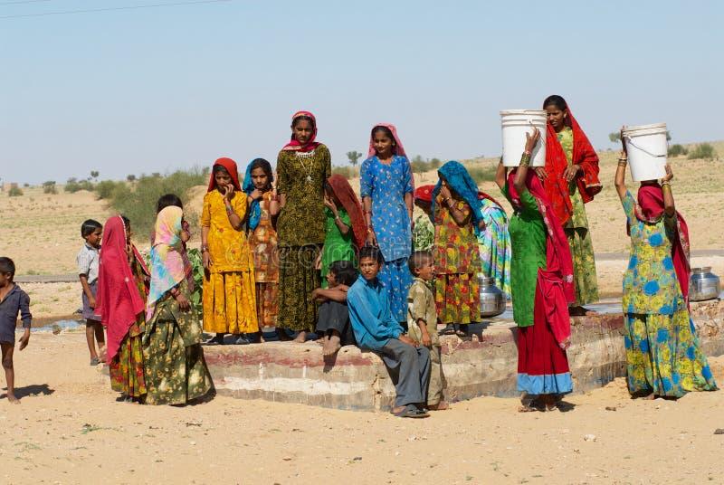 Il gruppo di giovani donne ed i bambini raccolgono bene l'acqua da un lato pubblico della strada nel grande deserto del Thar in r fotografie stock