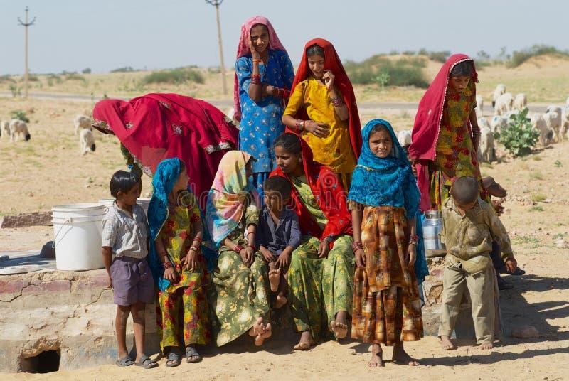 Il gruppo di giovani donne ed i bambini raccolgono bene l'acqua da un lato pubblico della strada nel grande deserto del Thar in r immagini stock