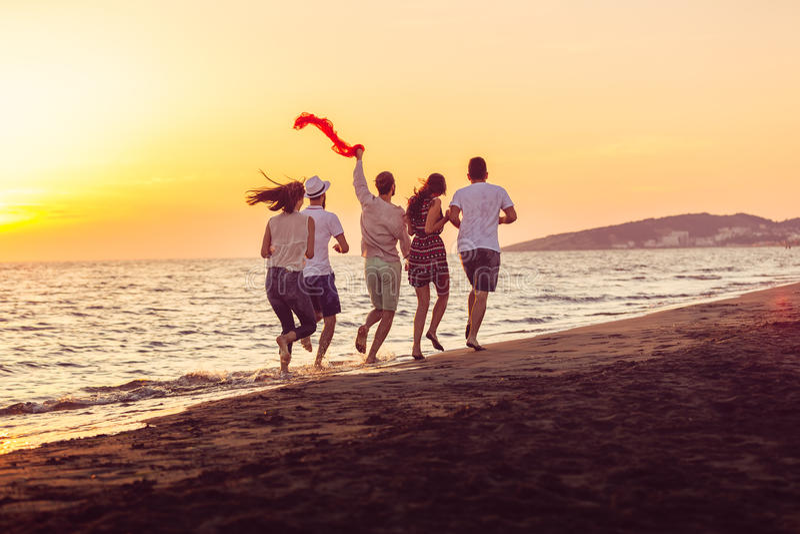 Il gruppo di giovani felici sta correndo sul fondo della spiaggia e del mare del tramonto immagine stock libera da diritti