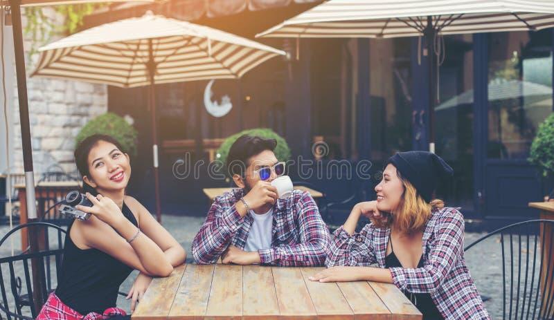 Il gruppo di giovani pantaloni a vita bassa che si siede in un caff?, giovani amici allegri divertendosi mentre richieda insieme  fotografia stock libera da diritti