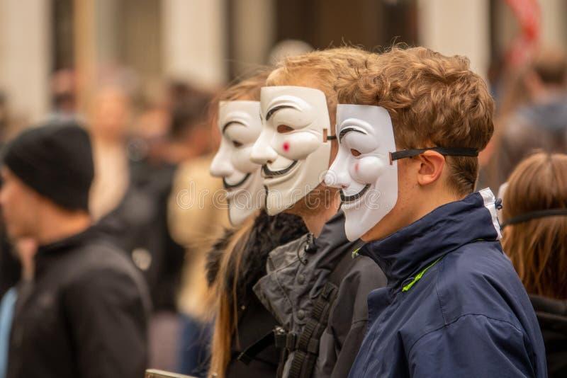 Il gruppo di giovani vestiti tutti nel nero esce sulla via dimostrare con le maschere anonime fotografia stock