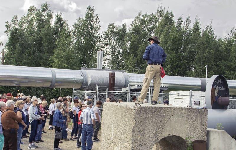 Il gruppo di giro ascolta Spiel all'epicentro della conduttura dell'Alaska immagini stock libere da diritti