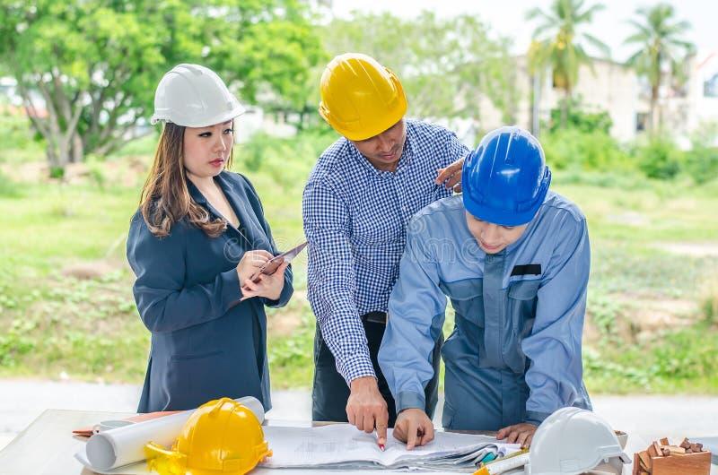 Il gruppo di ingegnere sta discutendo il piano della costruzione del progetto con il suo cliente di affari immagini stock libere da diritti