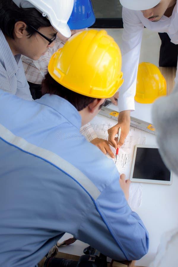 Il gruppo di ingegneria è incontrarsi, progettante i lavori di costruzione al cantiere/fuoco selettivo fotografia stock
