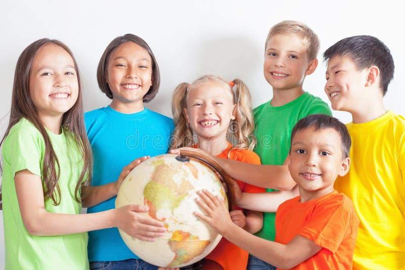 Il gruppo di internazionale scherza la terra del globo della tenuta immagine stock libera da diritti