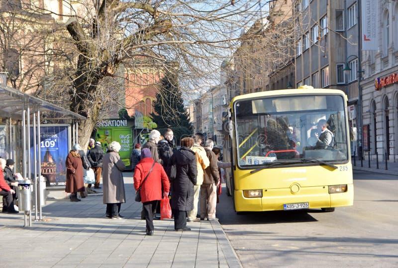 Il gruppo di persone che aspettano nella coda per entrare nel bus locale della città sull'autobus fermata la stazione fotografie stock libere da diritti