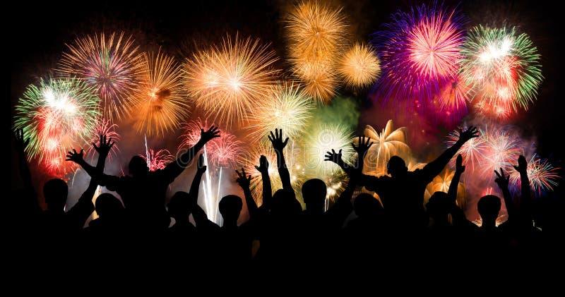 Il gruppo di persone che godono dei fuochi d'artificio spettacolari mostra in un carnevale o in una festa