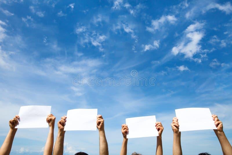 Il gruppo di persone che tengono la carta in bianco vuota firma fotografia stock libera da diritti