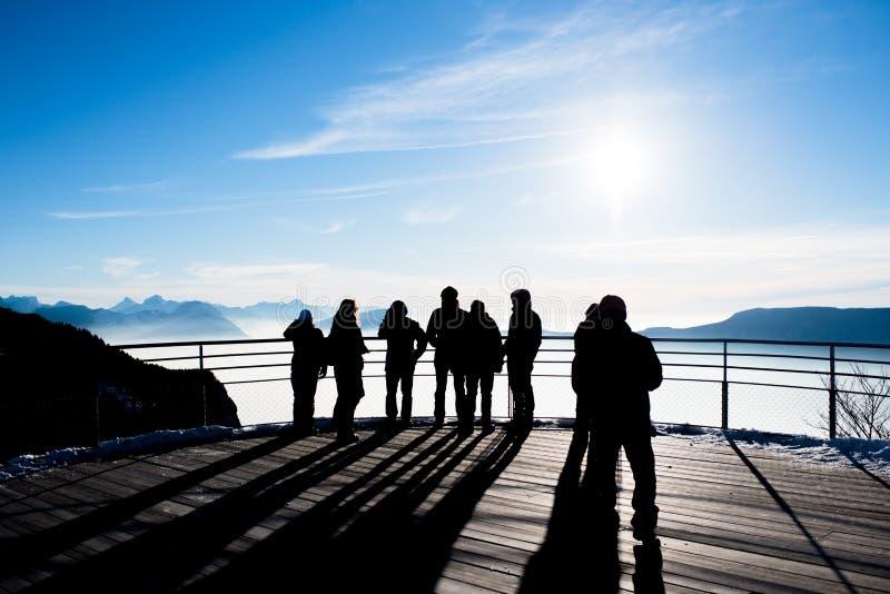 Il gruppo di persone sulla piattaforma panoramica che esamina la bella vista francese dell'inverno delle alpi abbellisce con il s immagine stock