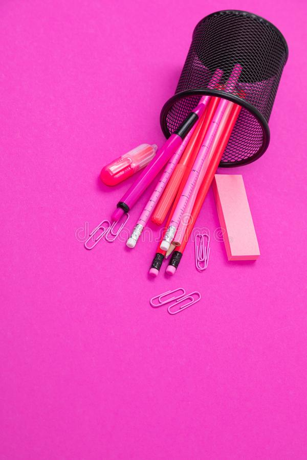 Il gruppo di prodotti rosa della cancelleria di colore è sparso dal recipiente della matita dall'alto al basso sul fondo di rosa  fotografie stock