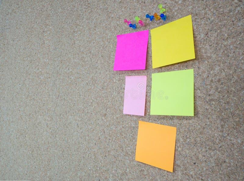 Il gruppo di puntine da disegno appuntate e le note di memorandum su sughero imbarcano fotografia stock libera da diritti
