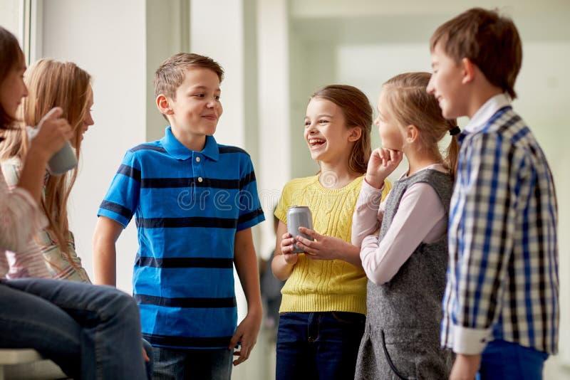 Il gruppo di scuola scherza con le latte di soda in corridoio fotografia stock libera da diritti