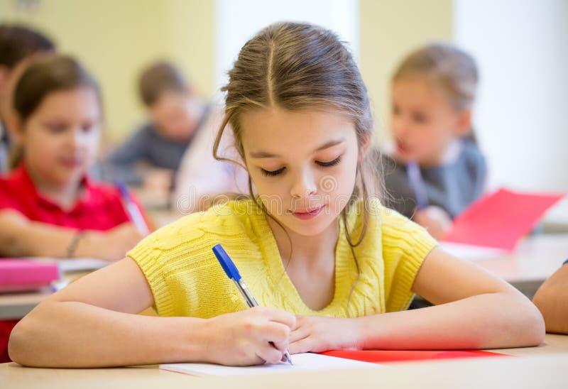 Il gruppo di scuola scherza la prova di scrittura in aula fotografia stock