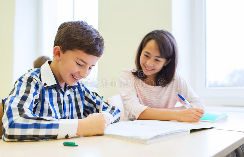 Il gruppo di scuola scherza la prova di scrittura in aula fotografia stock libera da diritti