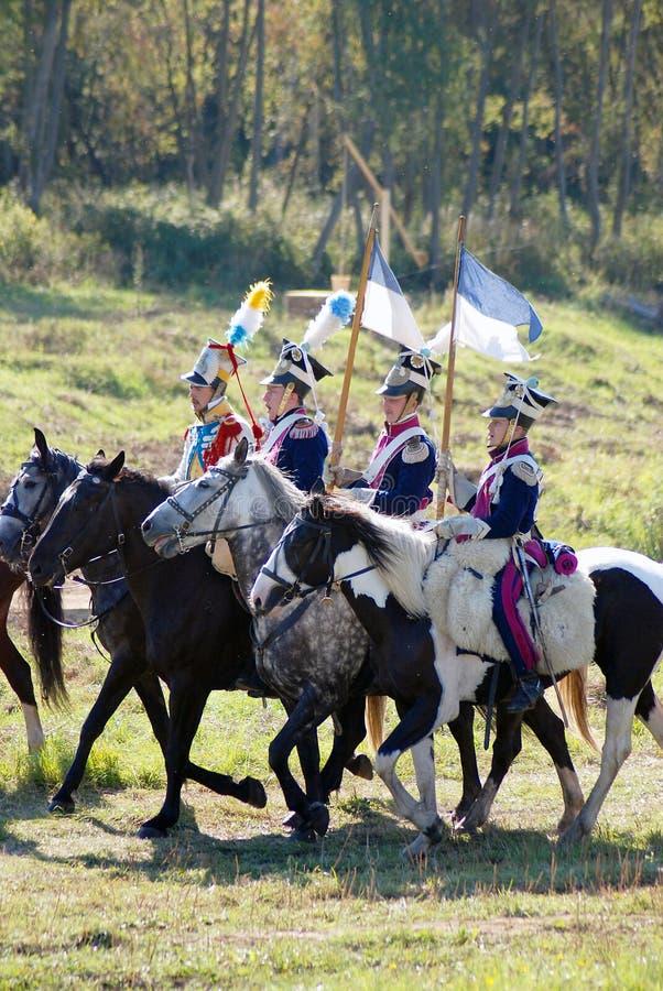 Il gruppo di soldati-reenactors monta i cavalli, due uomini porta le bandiere fotografie stock