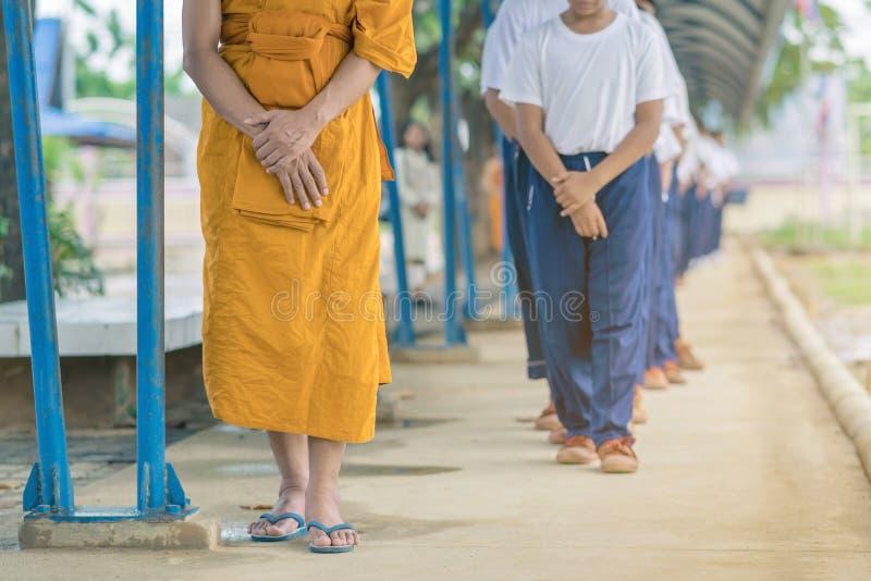 Il gruppo di studenti prova a meditare per la pace dello spirito dalla passeggiata con il monaco buddista immagini stock