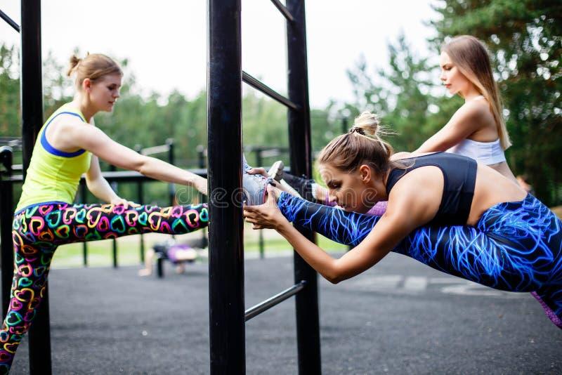 Il gruppo di tre belle giovani donne che fanno sport nel giorno soleggiato nel parco sport di sanità e di felicità all'aperto fotografia stock