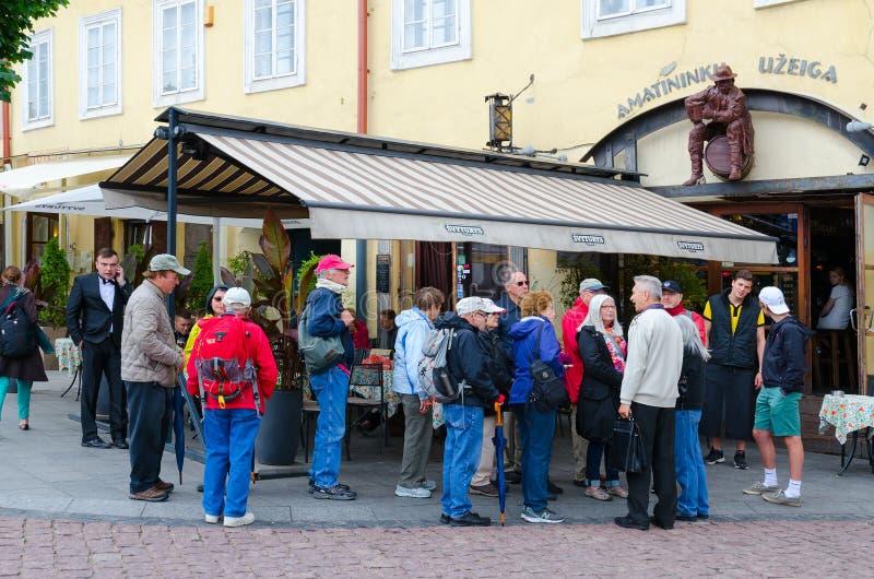 Il gruppo di turisti si avvicina al piccolo caffè in Città Vecchia, Vilnius, Lithuani immagini stock