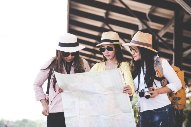 Il gruppo di viaggiatore delle donne dell'Asia ed il viaggio turistico backpack la mappa della tenuta e l'attesa in un binario de fotografie stock