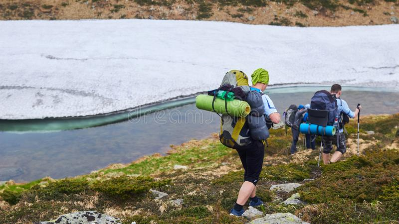 Il gruppo di viandanti che camminano in montagne fotografia stock