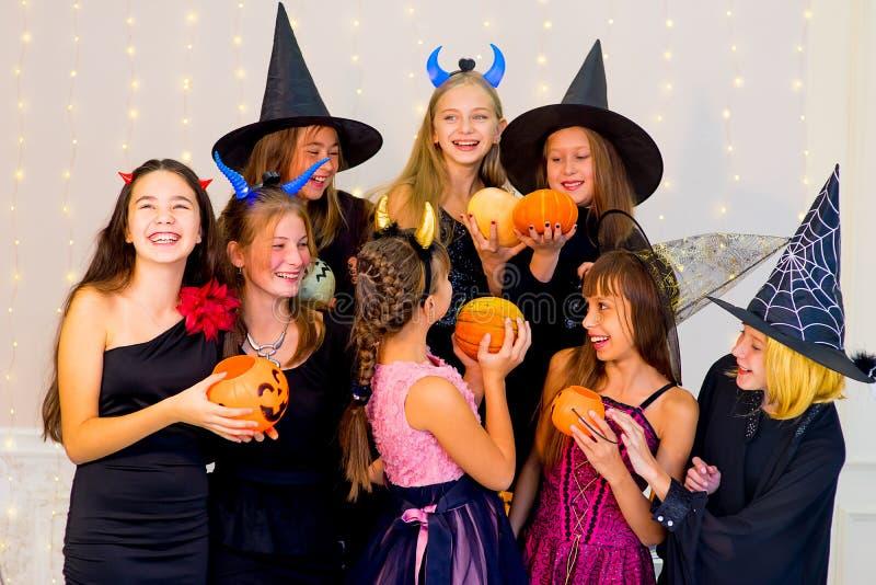 Il gruppo felice di adolescenti in Halloween costumes la posa sulla macchina fotografica fotografia stock libera da diritti