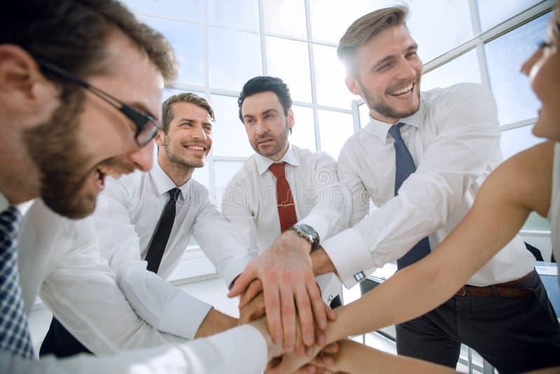 Il gruppo felice di affari collega insieme le loro mani immagine stock