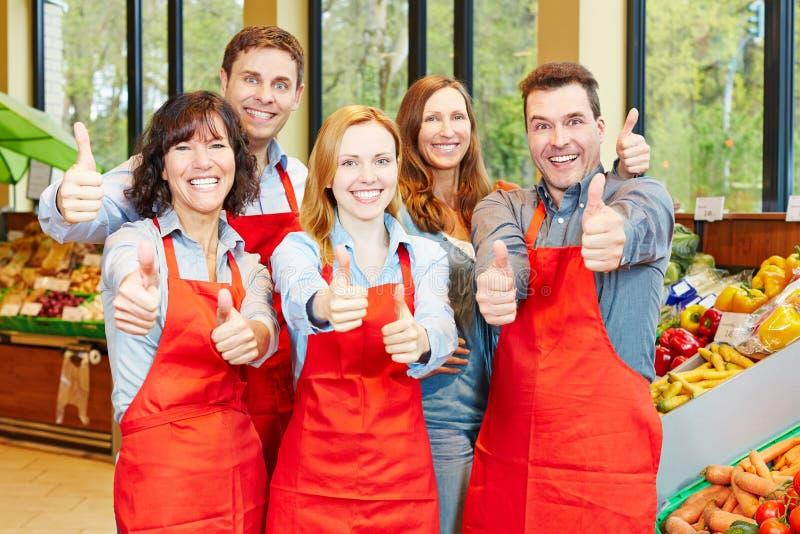 Il gruppo nella tenuta del supermercato sfoglia su immagine stock