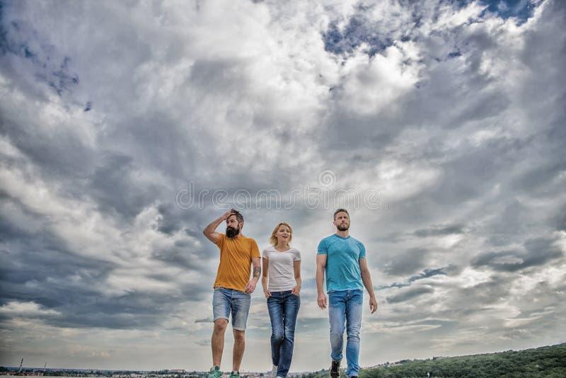Il gruppo unito si muove espressamente in avanti Fondo drammatico del cielo nuvoloso delle passeggiate della donna e degli uomini fotografia stock libera da diritti