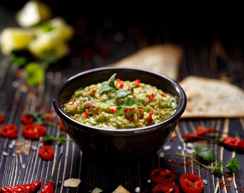 Il guacamole è una immersione messicana tradizionale fatta dell'avocado, della cipolla, dei pomodori, del coriandolo, dei peperon fotografia stock libera da diritti