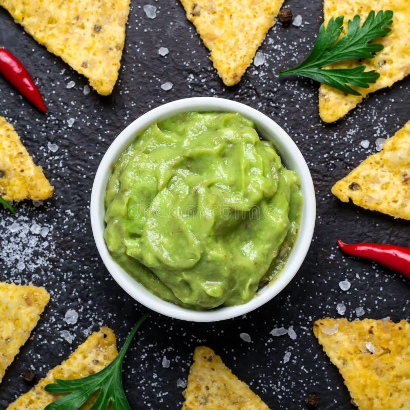 Il guacamole ed il cereale scheggia il primo piano Alimento dell'America latina tradizionale su fondo nero immagini stock libere da diritti