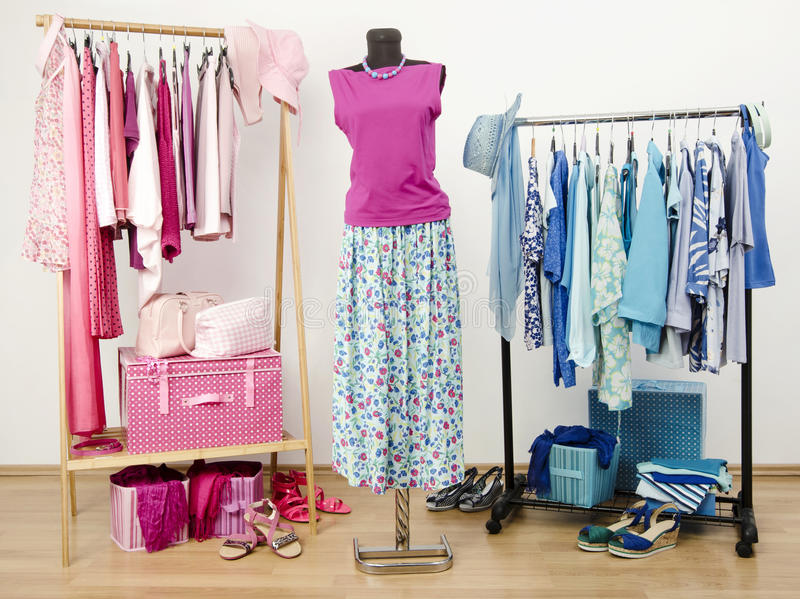 Il guardaroba con con i vestiti rosa e blu ha sistemato sui ganci Attrezzatura sveglia di estate su un manichino immagine stock