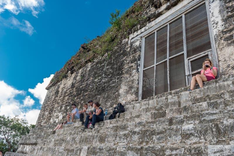IL GUATEMALA - 7 NOVEMBRE 2017: La gente sta sedendo sulla piramide e sul tempio nel parco di Tikal Oggetto facente un giro turis fotografie stock libere da diritti