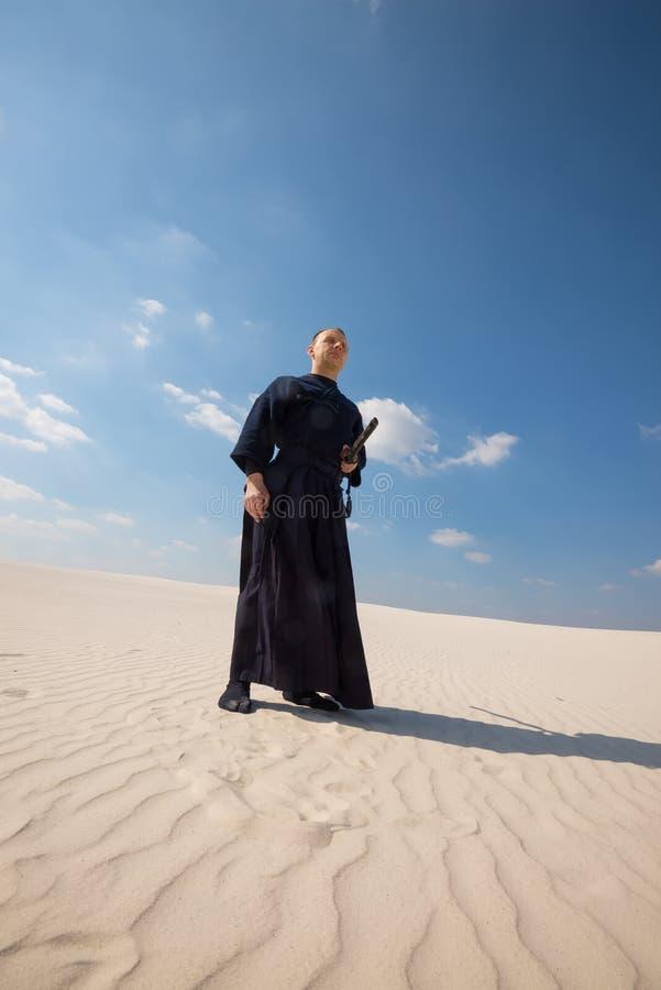 Il guerriero dell'uomo in vestiti giapponesi tradizionali sta in deserto fotografie stock
