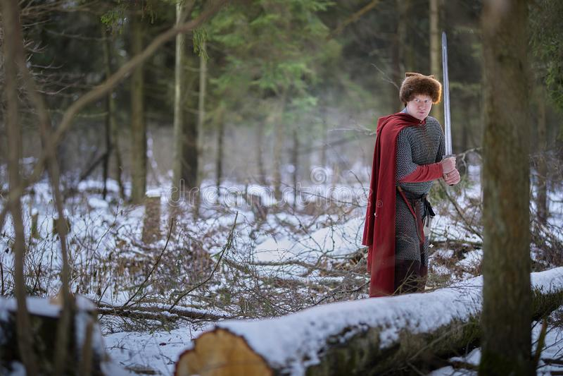Il guerriero medievale sta nella foresta dell'inverno immagini stock libere da diritti