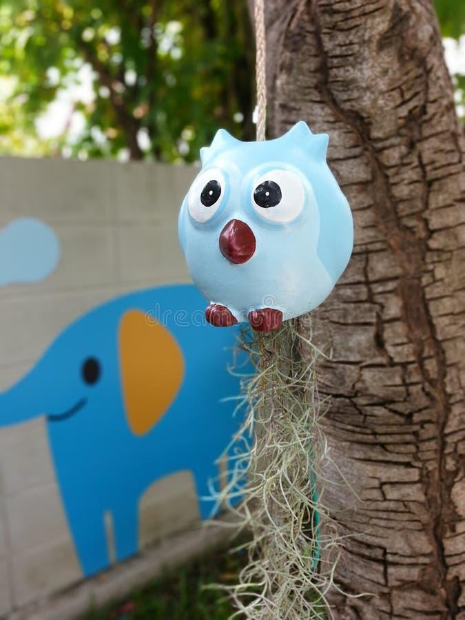 il gufo blu sta appendendo sotto l'albero immagini stock libere da diritti