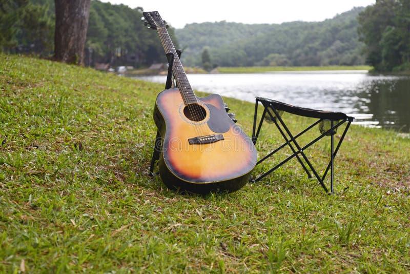 Il guita con nella sedia che si accampa nel lago, fotografie stock