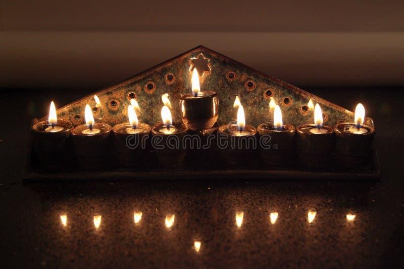 Il hanukiah ceramico si è acceso con 4 candele e shamash con la vista frontale fotografie stock