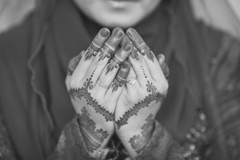 Il hennè e la fede nuziale sulla sposa passano, pregano per la sessione di doa fotografia stock