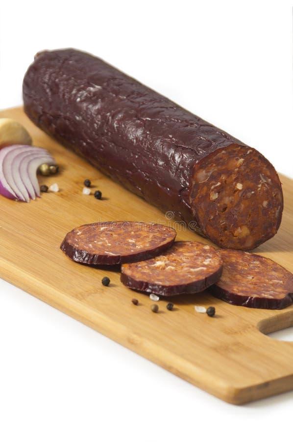 Il hickory ha fumato la salsiccia affettata del manzo isolata su fondo bianco - kobasica di Kranjska fotografie stock libere da diritti