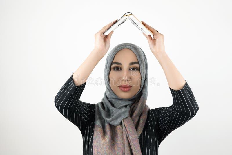 Il hijab d'uso del turbante della giovane bella donna musulmana promettente, libro della tenuta del foulard in sue mani al di sop immagini stock libere da diritti