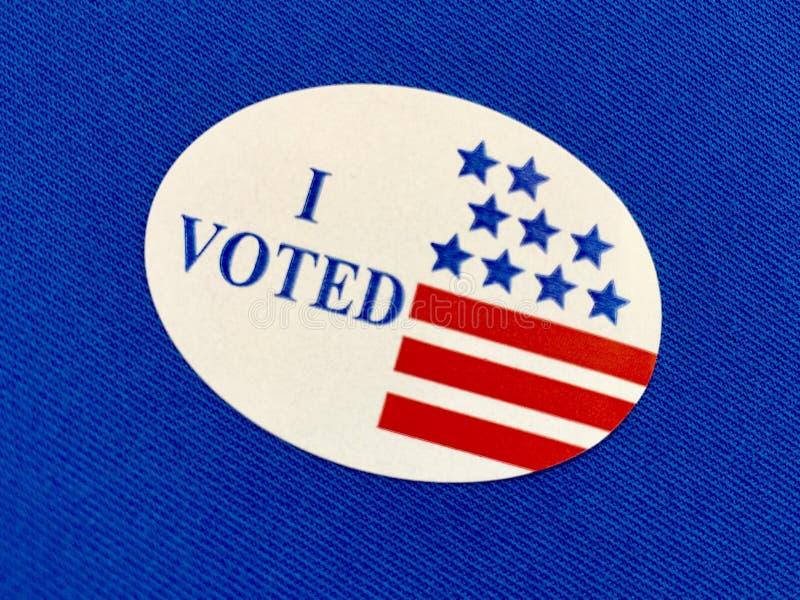 Il ` I ha votato l'autoadesivo del ` su tessuto blu immagini stock