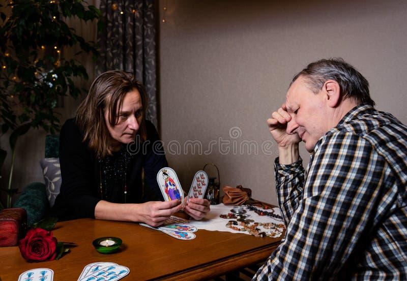 Il indovino contiene due carte e le mostra al cliente Un uomo sembra perplesso immagine stock