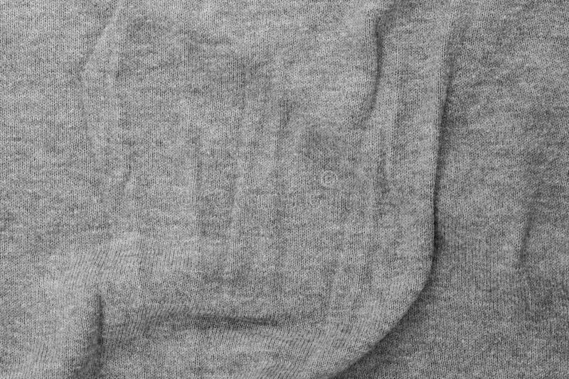 Il jersey piegato grigio tricotta la struttura del fondo del tessuto immagini stock