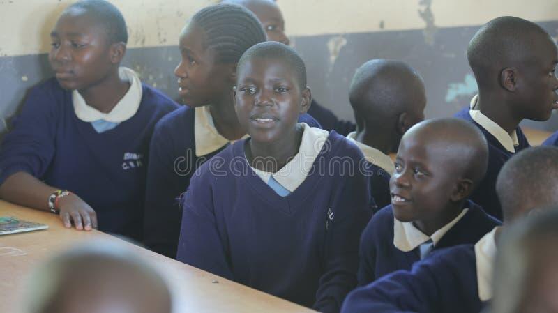 IL KENYA, KISUMU - 23 MAGGIO 2017: Gruppo di bambini africani che si siedono nell'aula e che esaminano macchina fotografica Appla immagine stock libera da diritti