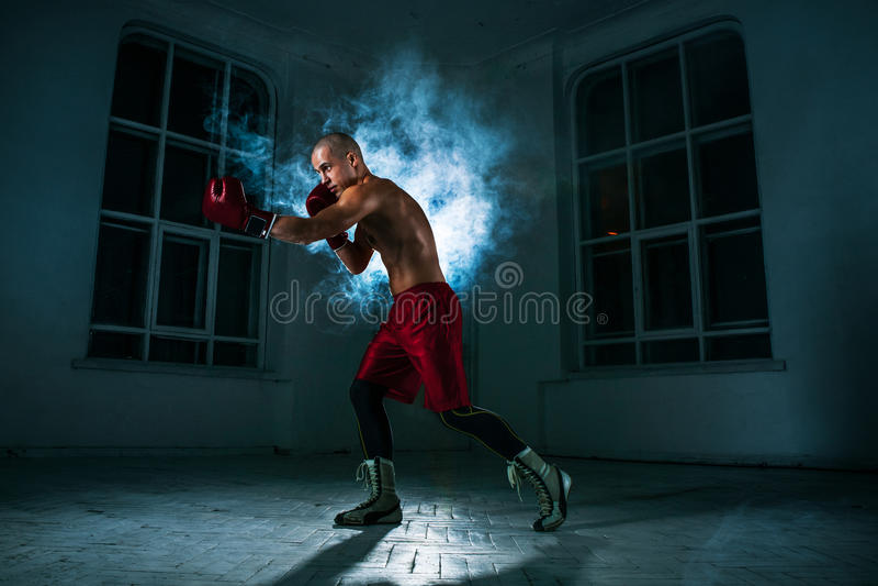 Il kickboxing del giovane in fumo blu immagine stock