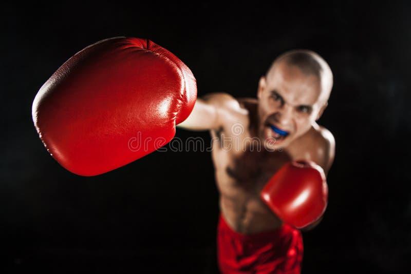 Il kickboxing del giovane sul nero con il kapa in bocca immagini stock