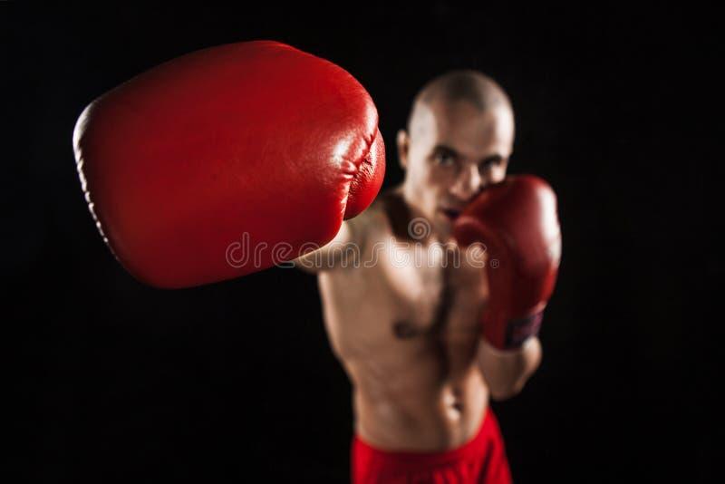 Il kickboxing del giovane sul nero con il kapa in bocca immagine stock