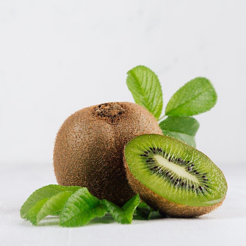 Il kiwi verde maturo con la metà ha tagliato e flusso di goccia del succo giù e giovani foglie sul bordo di legno bianco come l'e fotografia stock libera da diritti
